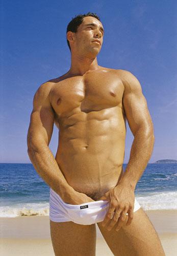 Hombre semi desnudo en la playa con traje de baño Bikini